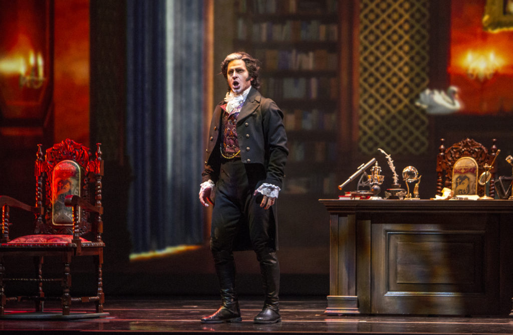 Baritone Andrew Garland as the compulsive, domineering book collector, Baron Otto von Schott, in the library of his ancestral fortress.